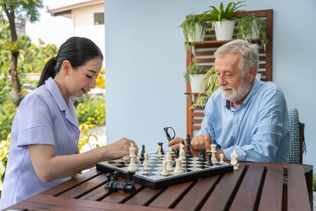 Elderly playing chess with nurse caregiver in nursing home for leisure Stock Photo