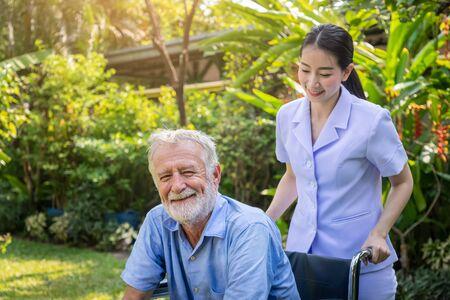 Happy nurse take care elderly man on wheelchair in garden at nursing home looing camera