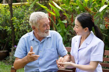 Happy nurse holding elderly man hand in garden at nursing home talking