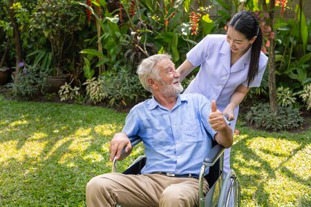 Happy nurse take care elderly man on wheelchair in garden at nursing home with thumb up Stock Photo