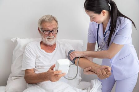 Happy nurse checking and measuring elderly man blood pressure with device in bedroom at nursing home