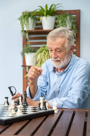 Elderly concentrate and playing chess in nursing home for leisure