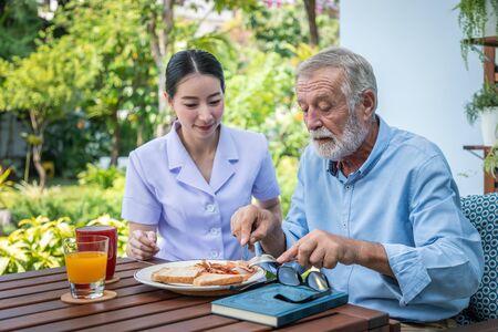 Nurse assist elderly senior man to eat breakfast at nursing home