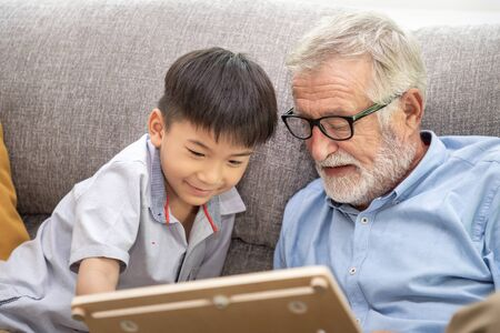 Happy boy grandson playing game with old senior man grandfather at home Stock Photo