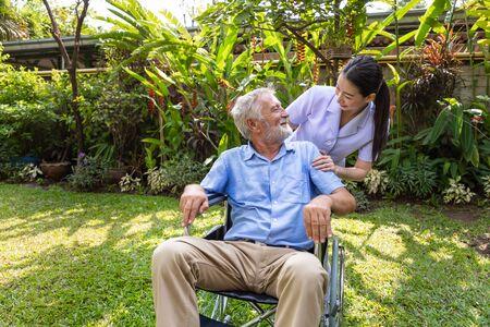 Happy nurse take care elderly man on wheelchair in garden at nursing home