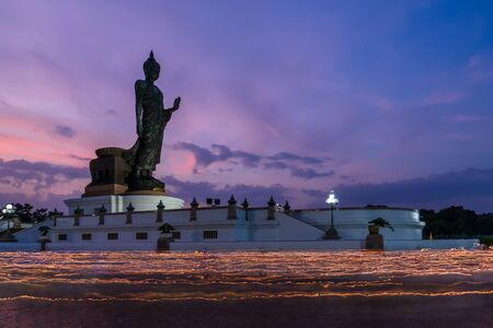 Candle procession ceremony around buddha statue in twilight on Vesak day or Buddha Birthday at Phuttha Monthon Buddhist park, Nakhon Pathom, Thailand 写真素材