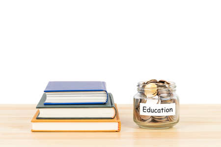 Coins in glass jar with label on wooden desk with book stack on white background, concept saving for education and scholarship