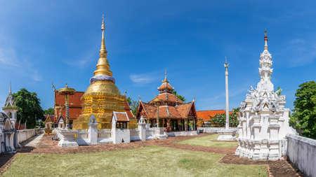 Golden pagoda and Buddha pavilion at Wat Pong Sanuk temple in Lampang, north of Thailand, panorama Imagens