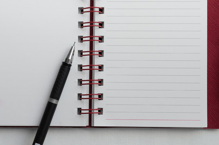 Wirebound Notebook Open with Lined Paper and Black Pen. Stock Photo