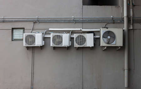 Compressors of air conditioning fixed to a dirty wall background.