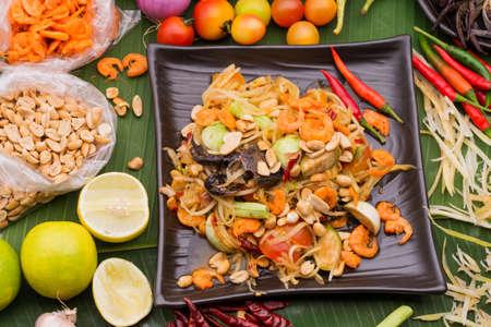 Thai papaya salad and ingredients on green leafs
