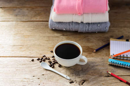 White coffee cup With black coffee and a pink white gray knit sweater and a pencil book on an old wooden table with the light of the sunshine.