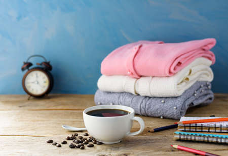 White coffee cup with black coffee and a knit sweater on an old wooden table. Blue wall background
