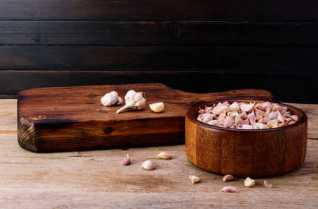 Garlic. Fresh garlic in a wooden bowl with a cutting board, placed on an old wooden table, black wood wall background. Reklamní fotografie