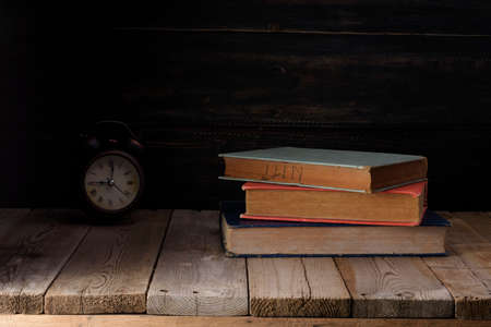 Old books and alarm clocks are placed on the old wooden table.