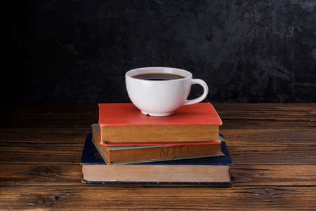 White coffee cup with dark black coffee And old books And the clock is arranged on an old wooden table and a black wooden wall.