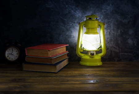 Old books and lamps alarm clock placed on old wooden table black wall background