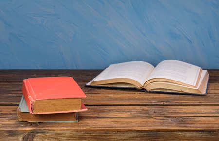 Red and blue old books placed on the old wooden table Blue wall background Stockfoto