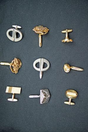 cufflinks: nine golden and silver cufflinks with black background.                   Stock Photo