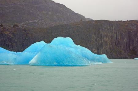 wasser: Ein blauer Eisberg im Wasser vor Bergen.