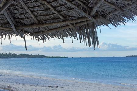 wasser: Perspektive eines unter dem Sonnenschirm Liegenden, Blick auf blaues Wasser.