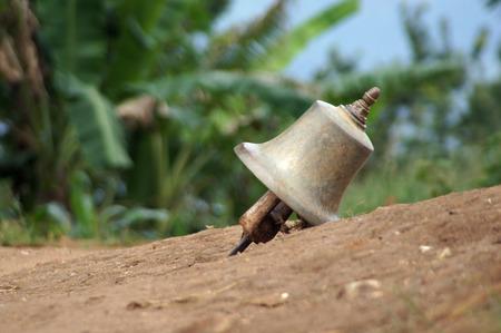 church bell: A church bell is in brown dust