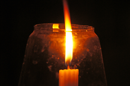 candlelit: A candle in a glass Stock Photo