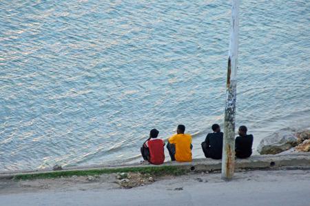 sit: Four men sit waiting on the shore