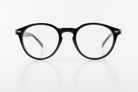 planar: black round frame of eyeglasses, vintage look, isolated white background, reflection