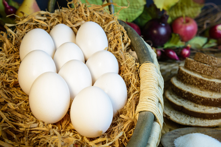 protien: still life white shell eggs  lay in hay basket, having whole wheat bread as a background, close up
