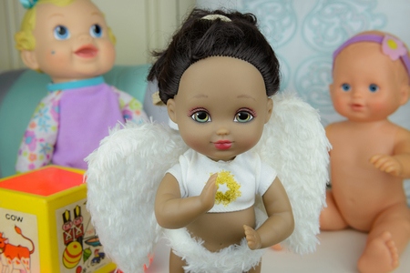 group of dolls, black skin doll in angle suit, white wings, girl Stock Photo