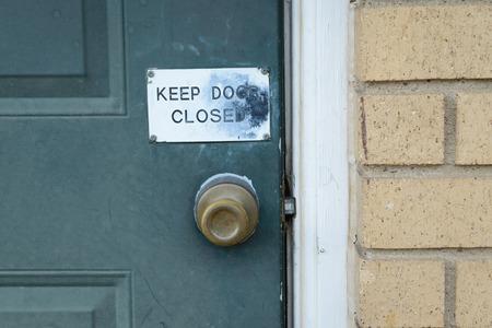 door knob: Keep door closed sign on green door with brass knob Stock Photo