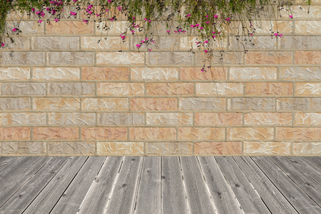 planar: background of random orange tone brick wall with small flower bush foreground, pattern, intersect wood floor Stock Photo