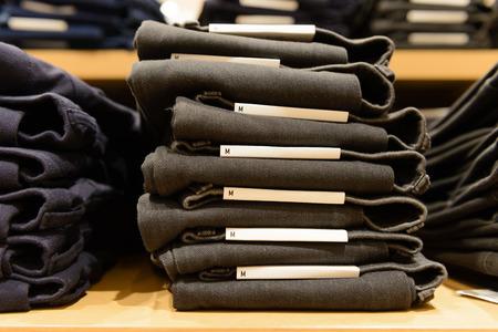 de vaqueros: heap of jeans on shelf, m size Foto de archivo