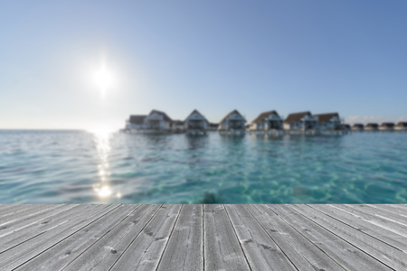 wood table surface infront luxury water bungalow ocean view