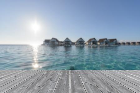 honeymooners: wood table surface infront luxury water bungalow ocean view