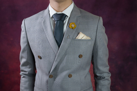 double breasted: Man in double breasted grey suit, plaid texture, blue necktie, flower brooch, and dot pattern handkerchief, close up