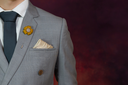 double breasted: Man in grey suit, plaid texture, blue necktie, flower brooch, and dot pattern handkerchief, close up