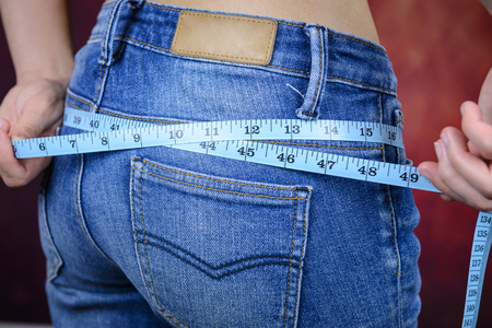 slim asian woman , wearing jeans, measuring her body shape, waist, buttocks 免版税图像 - 50757853