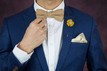 navy blue suit: Man in blue suit with coffee cream bowtie color, flower brooch, and dot pattern handkerchief, close up, adjusting bowtie