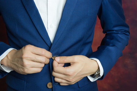 tailor suit: Man in blue suit two bottons, doing button