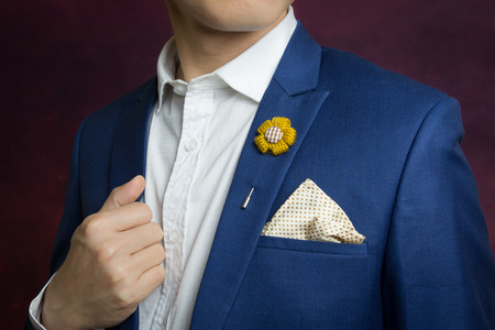 navy blue suit: Man in blue suit with  flower brooch, and dot pattern handkerchief, close up