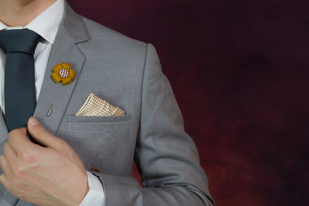 Man in grey suit, plaid texture, blue necktie, flower brooch, and dot pattern handkerchief, close up