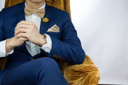 tailored: Man in blue suit with coffee cream bowtie color, flower brooch, and dot pattern pocket square sitting on cozy sofa