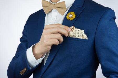 Man in blauw pak met koffieroom bowtie kleur, bloem broche, en puntpatroon pochet, close-up