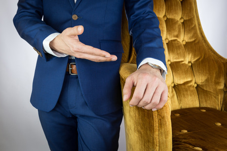 tailored: Man in blue suit standing beside yellow cozy sofa