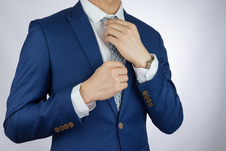tailored: businessman fitting up blue suit and necktie