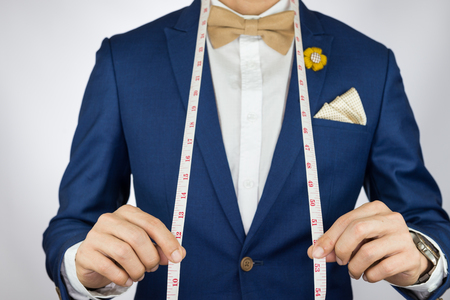 man measurement: Man in blue suit with coffee cream bowtie color, flower brooch, and dot pattern pocket square carry measurement tape