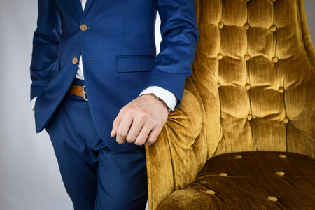 navy blue suit: Man in blue suit standing beside yellow cozy sofa