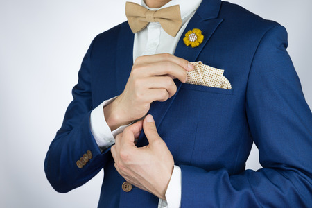 tailored: Man in blue suit with coffee cream bowtie color, flower brooch, and dot pattern pocket square, close up